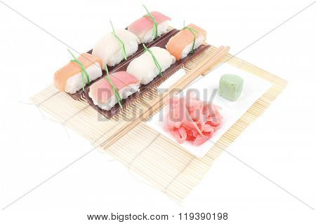 Japanese Cuisine - Different Types of Nigiri Sushi Tuna (maguro) Salmon (sake) and Eel (unagi) with Wasabi and Ginger on bamboo mat isolated over white background