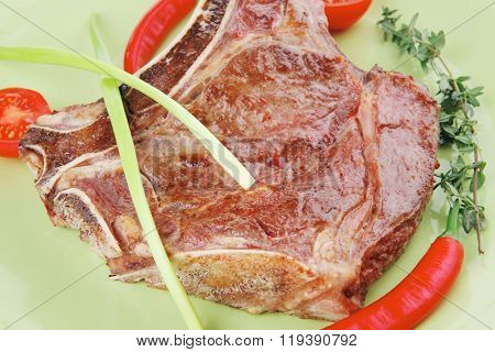 meat food roast rib on green dish with thyme pepper and tomato isolated over white background