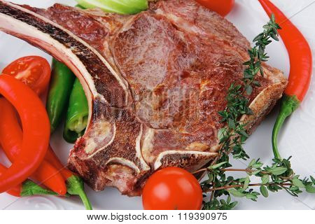 meat food roast rib on white dish with thyme pepper and tomato on wooden table