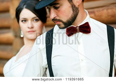 Thoughtful groom in hat with beard, mustache, bow tie and suspenders. Bride wearing white wedding dr