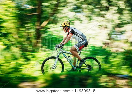 Aged Mountain Bike cyclist riding track at sunny day. Motion bl