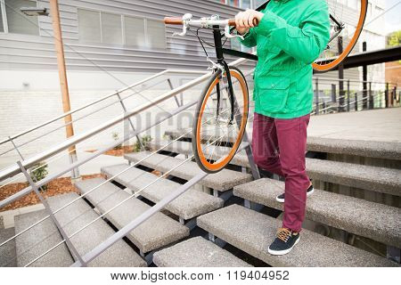 people, style, leisure and lifestyle - close up of man with fixed gear bike going downstairs