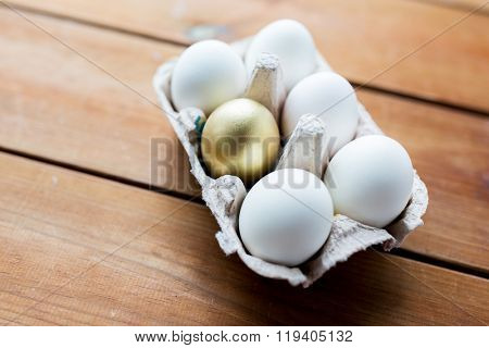 easter, food, cooking and object concept - close up of white and golden eggs in egg box or carton wooden surface