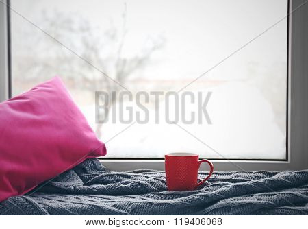 Red cup of tea, warm knitted plaid and pink pillow on windowsill, close up