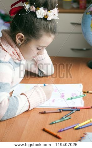 Little Beautiful Girl Draws Sitting At Table In Room