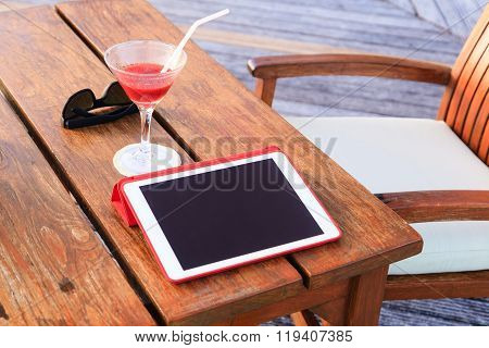cocktail, touch pad and glasses on beach