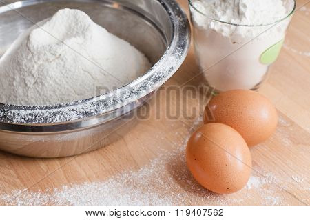 Flour in bowl and two eggs on wooden table background