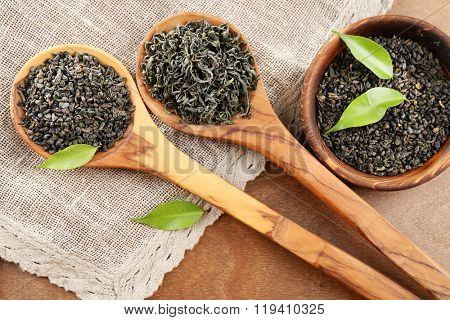Dry tea with green leaves in wooden spoons and bowl on wooden table background