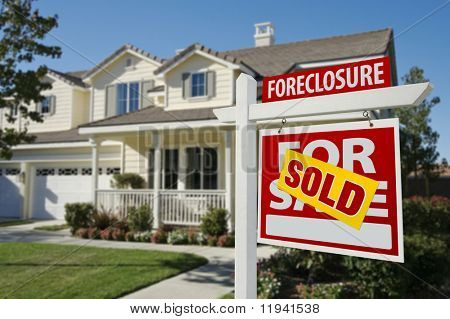 Sold Foreclosure Home For Sale Sign in Front of Beautiful House.