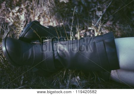 Woman Legs In Black Leather Boots On Grass And Autumn Leaves.  Beautiful Legs Girl In  Boots Sitting