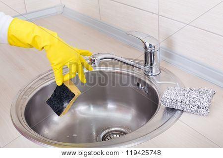 Hand With Sponge Above Kitchen Sink