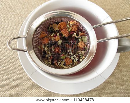 Herbal tea with fruits and flowers in tea strainer