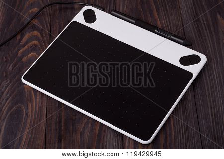 graphics tablet on wooden background