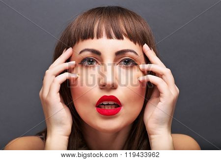 Model on a gray background beautiful makeup. Her arms near his head the pain the quarrel scandal anxiety on her face.