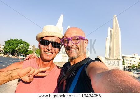Happy Couple Of Male Friends Taking Selfie At Bangkok Democracy Monument - Cheerful Tourists Guys -