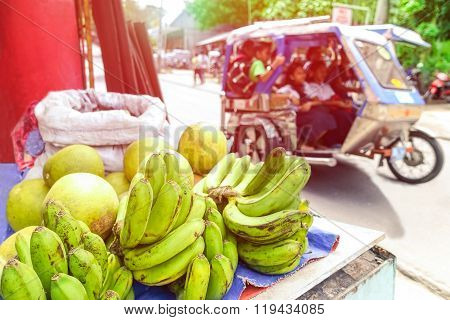 Close-up Of Bananas In Traditional Asian Market At The Roadside With Blurred Tricycle Vehicle -