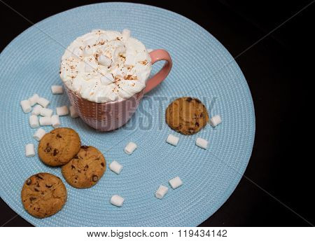 Pink cup of cocoa with marshmellows on light blue napkin