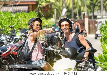 Happy Couple Sitting On Scooters Pointing During City Tour - Young Woman And Man Riding Motorcycle