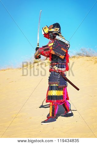 Man in samurai costume with sword running on the sand. Men in samurai armour running on the sand. Original Character