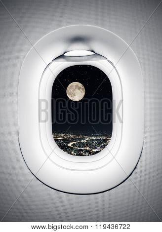 Night city under moon at airplane window