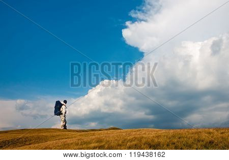 Man with backpack looking at a stormy sky