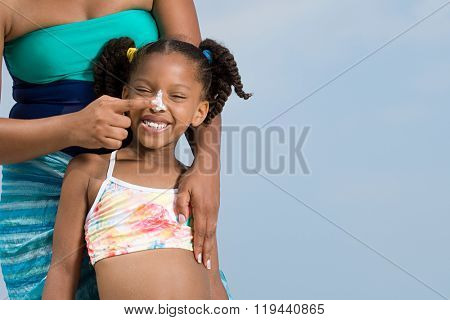 Mother applying suncream to daughters nose