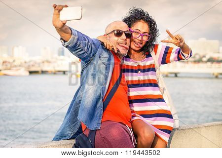 Funny Couple Taking Selfie Using Cell Phone At Pier With Ocean Background - Young Traveling people -
