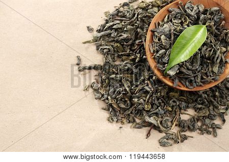 Scattered tea with green leaves in wooden spoon on burlap background
