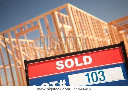 Vendido lote imobiliária sinal em casa nova enquadramento canteiro contra o céu azul profundo.