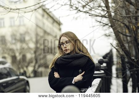 Beautiful blonde woman in glasses, coat near road at street