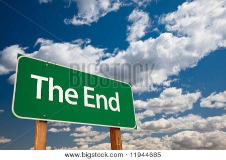 The End Green Road Sign with Copy Room Over The Dramatic Clouds and Sky.