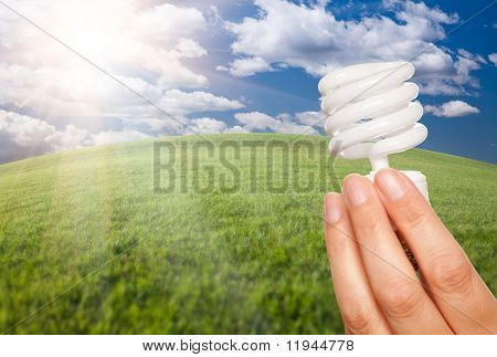 Female Hand Holding Energy Saving Light Bulb Over Arched Horizon of Grass Field, Clouds and Sky.