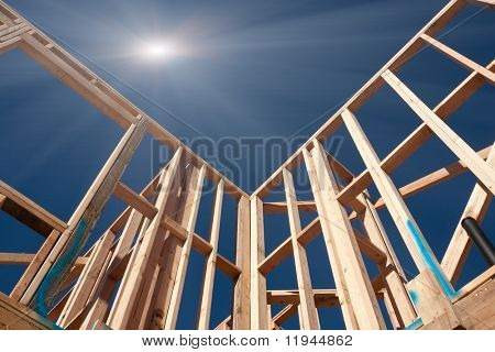 New Construction Framing Abstract with Sunburst Over Clear Blue Sky.