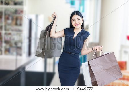 Asian Woman Taking A Walk In The Mall And Holding A Lot Of Shopping Bags
