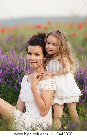 Happy mother and daughter in a field of blooming lavender