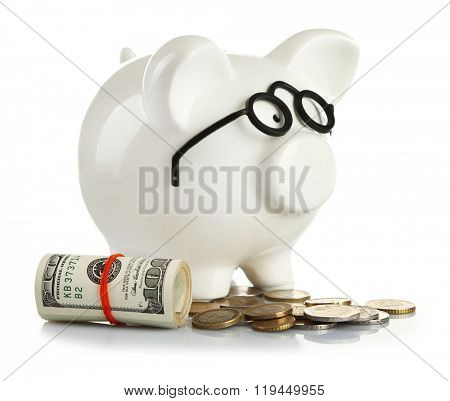 Piggy bank in glasses with dollars and coins isolated on white