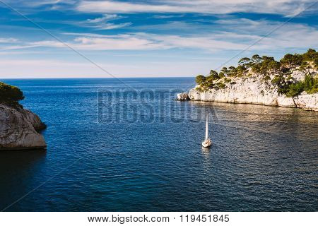 Yacht leaves from bay to open sea in Calanques on the azure coas