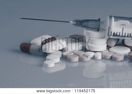 Syringe drugs and many tablets blue effect