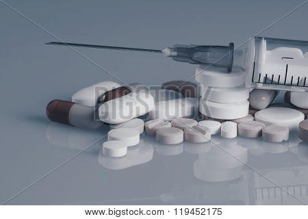Syringe drugs and many tablets blue effect