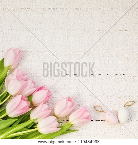 Pink tulips and decorative Easter eggs on white tablecloth. Top view, copy space
