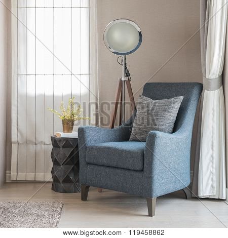 Classic Blue Sofa Style With Grey Pillows And Modern Lamp On Wooden Floor