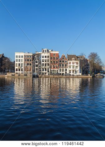 AMSTERDAM NETHERLANDS - 17TH FEBRUARY 2016: Buildings along Staalkade street in Amsterdam. Part of the Amstel canal can be seen.