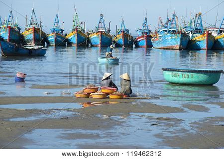 Two women sit with their catch amid the fishing boats. Fish haven in Mui Ne, Vietnam