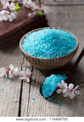 Mineral bath salts, towels and flowers on the old wooden table. Shallow DOF