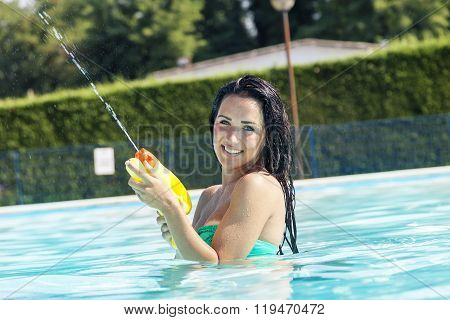 pretty girl playing with water guns in pool