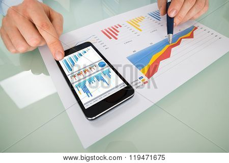 Businessperson Hand Analyzing Graph