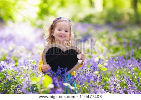 Little Girl With Blank Board In Flower Field