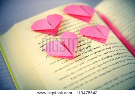 Heart bookmark for book on wooden table closeup