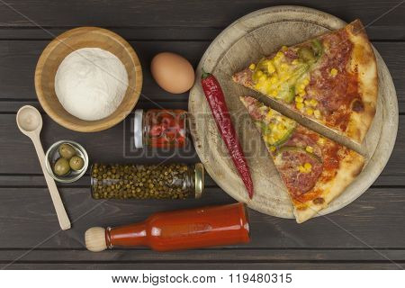 Homemade pizza. Portions of pizza on a dark wooden table.