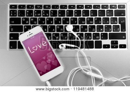 White cellphone with romantic screensaver and headphones on laptop